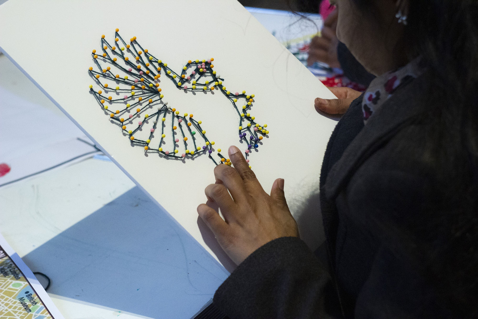 Child creating artwork of a bird.